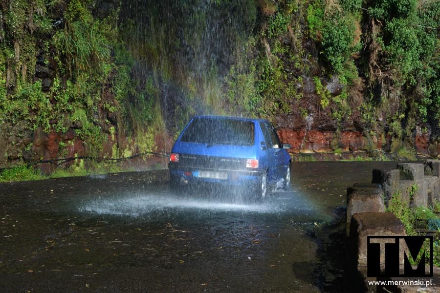 Samochód przejeżdżający przez wodospad na drodze