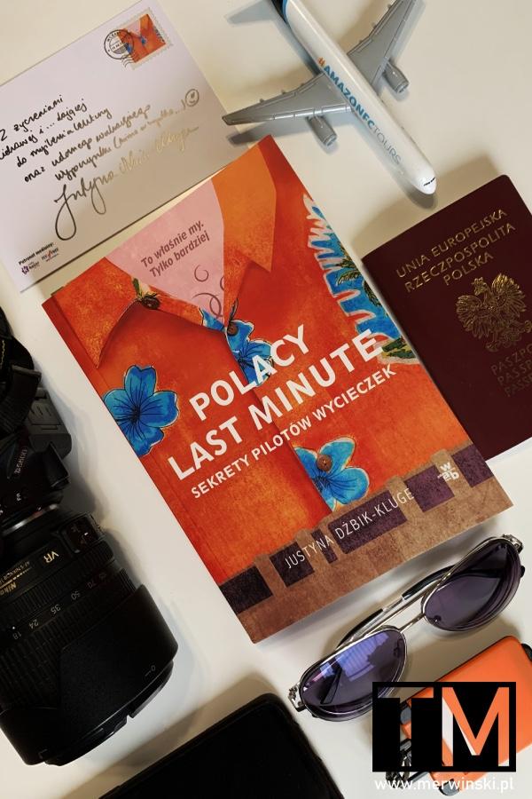 """Książka """"Polacy last minute"""" na stole z gadżetami podróżnymi"""