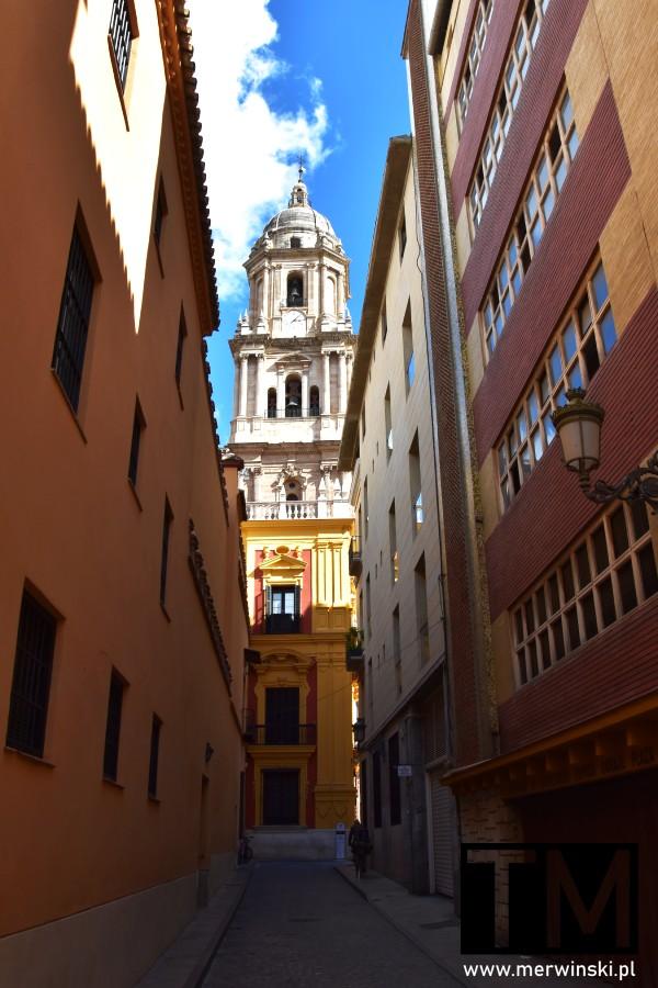 Widok na wieżę katedry w Maladze z wąskiej uliczki